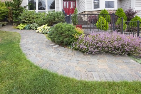Custom Designed Landscaping With Stone Path, Shrubs, Patio, And Beautiful Multi-colored Flowers