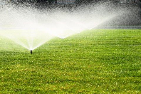 Sprinkler System Watering Green Lawn