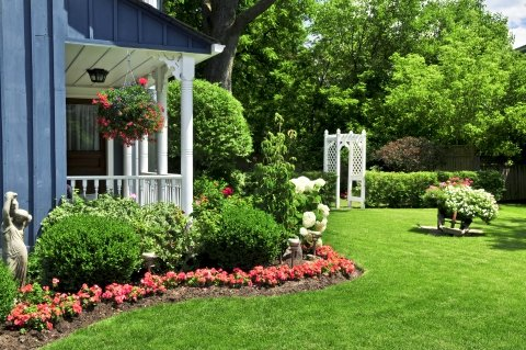 A Back Yard With Covered Porch And Hanging Flower Baskets With Manicured Lawn, Flower Beds, Shrubs, Statues, And A Trellis.