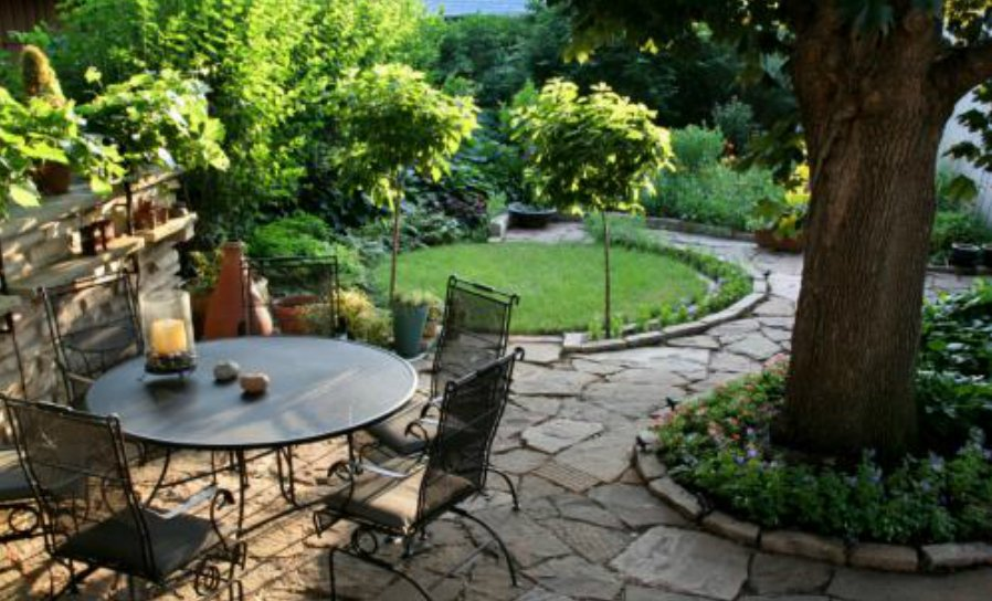Outdoor Stone Patio Seating Area With Table And Chair, Tree With Garden Bed Surrounding It, And Manicured Lawn