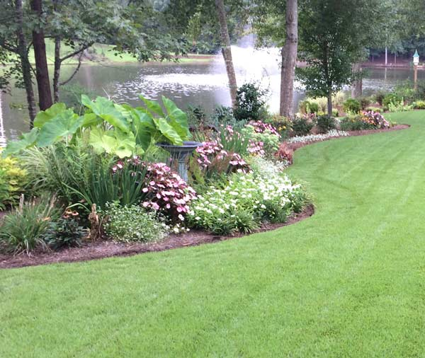Custom Designed Landscaping With Flowers Manicured Lawn And Lake