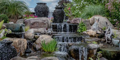 Custom Designed Water Feature With Rocks, Jugs, And Plants