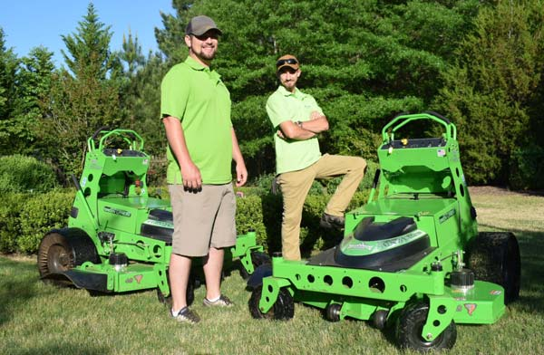 Local Landscaping Company Team Members With Quite Electric Mowers In Nice Landscape