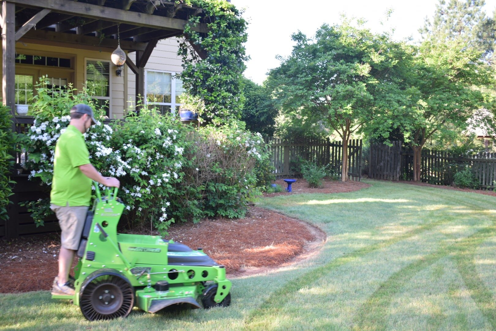 Man Driving Quiet Electric Mower Around Garden Bed On Manicured Lawn