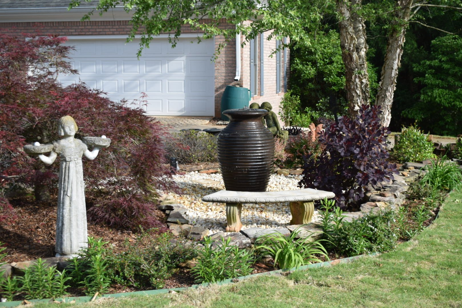Custom Designed Landscaping With Garen Beds, Shrubs, And Statues