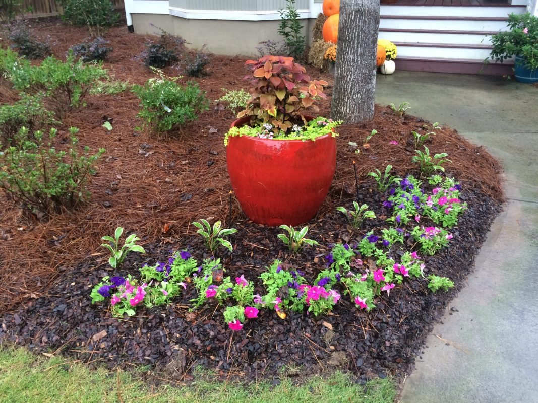 Custom Designed Landscaping With Red Planter, Flowers, And Shrubs